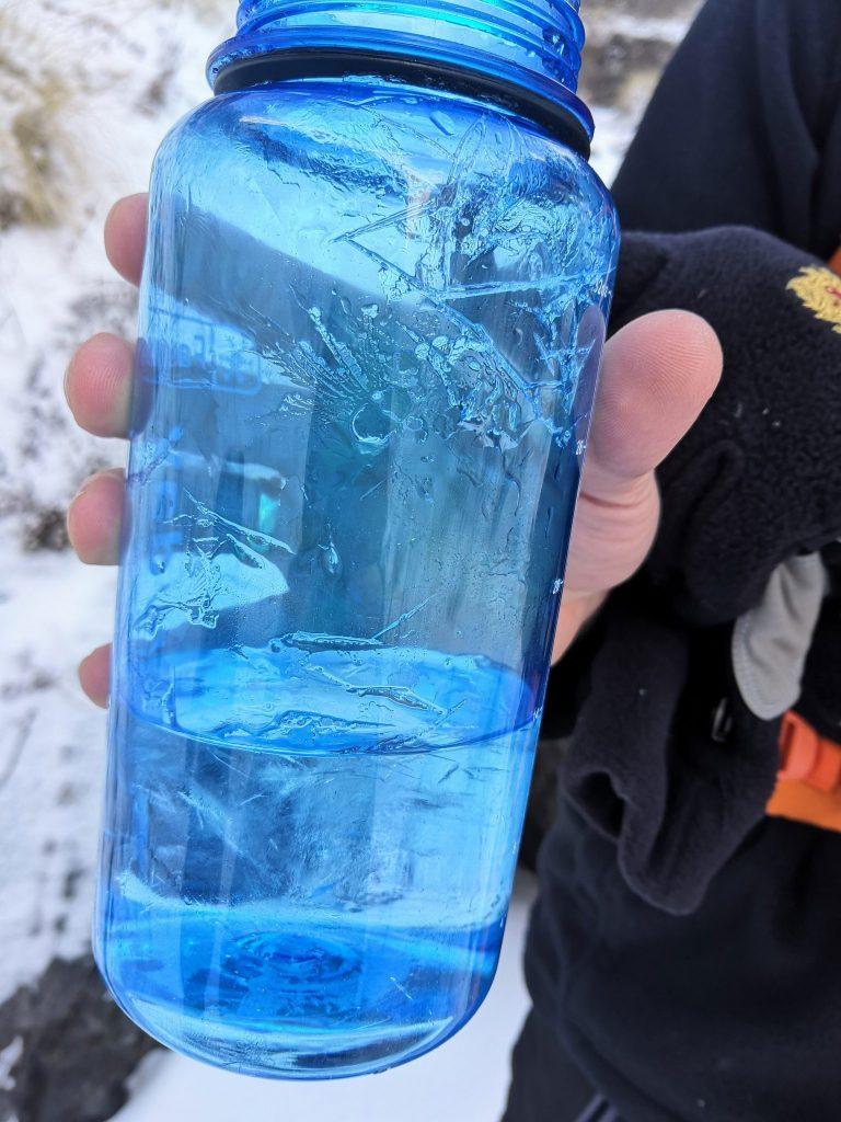 Gefrorene Wasserflasche beim Trekking in Nepals Höhe