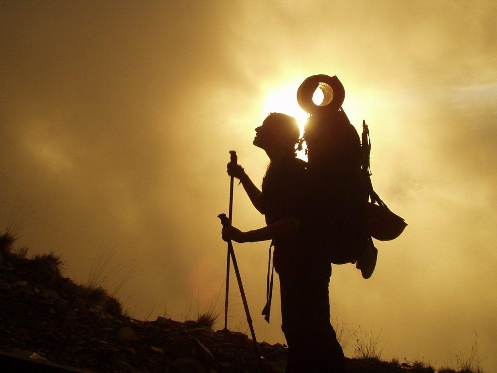 Frau beim Trekking blickt nach oben zum Gipfel